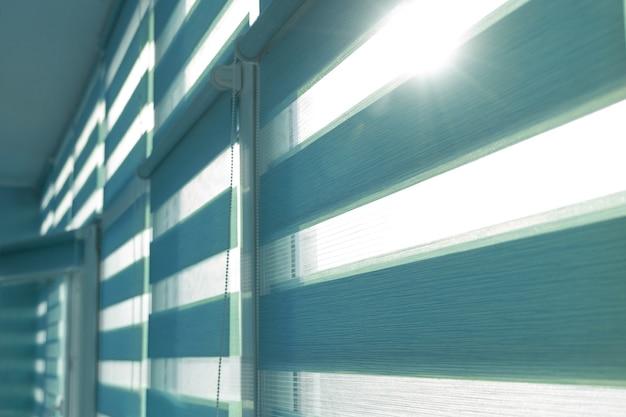 Close up van gekleurde stoffen rolgordijnen op venster. rol gordijnen.