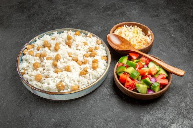 Close-up van gekruide spliterwten en rijst zuurkool en salade op donker