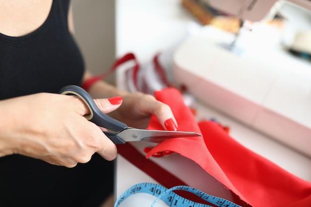 Close-up van gekwalificeerde vrouwelijke naaister die rode doek met een schaar snijdt