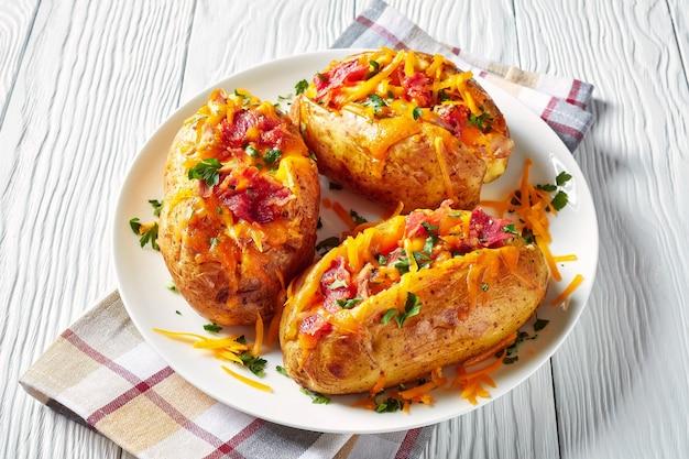 Close-up van geladen vers gebakken hete aardappelen met krokant gebakken spek, getrokken kipfilet en gesmolten cheddar kaas op een witte schotel op een houten tafel, horizontale weergave van bovenaf
