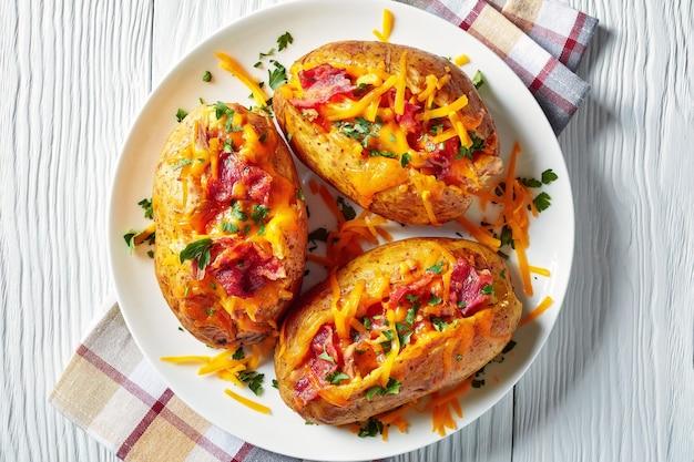 Close-up van geladen vers gebakken hete aardappelen met krokant gebakken spek, getrokken kipfilet en gesmolten cheddarkaas op een witte schotel op een houten tafel, uitzicht van bovenaf, flatlay