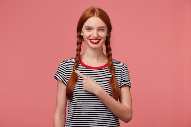 Close-up van gelukkig geïnspireerde roodharige tienermeisje shows met wijsvinger aan de linkerkant, is opgetogen over het product, adviseert op te letten, toont plaats voor uw advertentie of promotietekst