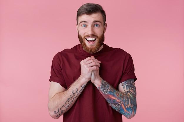 Close-up van gelukkig knappe bebaarde jonge man met getatoeëerde hand, zag iets leuks en glimlachen, kijkend naar camera geïsoleerd op roze achtergrond.
