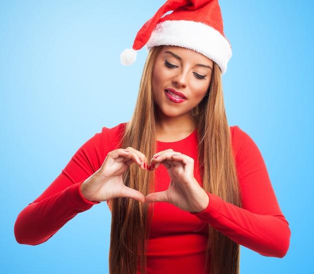 Close-up van gelukkig meisje het maken van een hart met haar handen