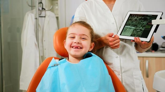 Close up van gelukkig meisje patiënt kijken camera lachen, wachten op pediatrische stomatologist in tandheelkundige unit. kind liggend op stomatologische stoel glimlachend naar webcam terwijl dokter praat met moeder