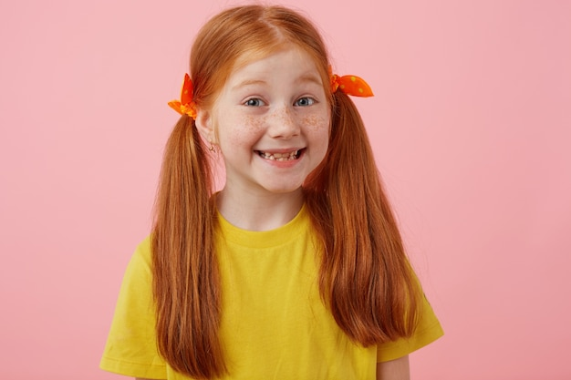 Close-up van gelukkig petite sproeten roodharig meisje met twee staarten, breed glimlachend en ziet er schattig uit, draagt in geel t-shirt, staat op roze achtergrond.