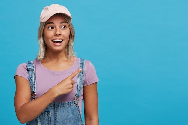Close-up van gelukkig verbaasde blonde jonge vrouw draagt roze pet, violet t-shirt en denim jumpsuit ziet er verbaasd uit en wijst naar de zijkant over de blauwe muur