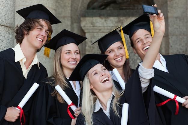 Close-up van gelukkige afgestudeerden die een foto van zichzelf nemen