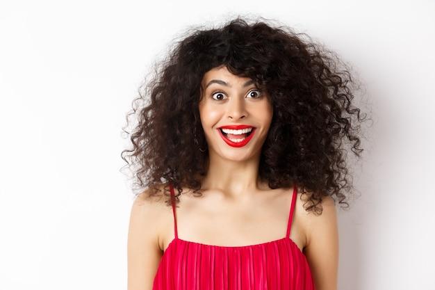 Close-up van gelukkige dame met krullend haar en rode lippen, wenkbrauwen optrekken en verbaasd kijken naar de camera, staande op een witte achtergrond.
