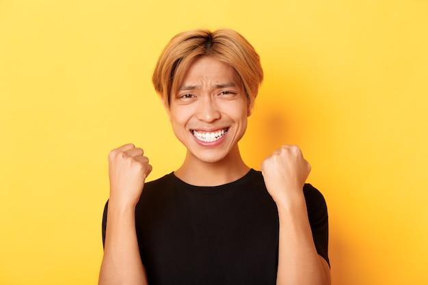 Close-up van gelukkige gelukkige aziatische kerel die prijs wint, vuistpompgebaar maakt en tevreden glimlacht, zegevierend over prestatie, staande gele muur