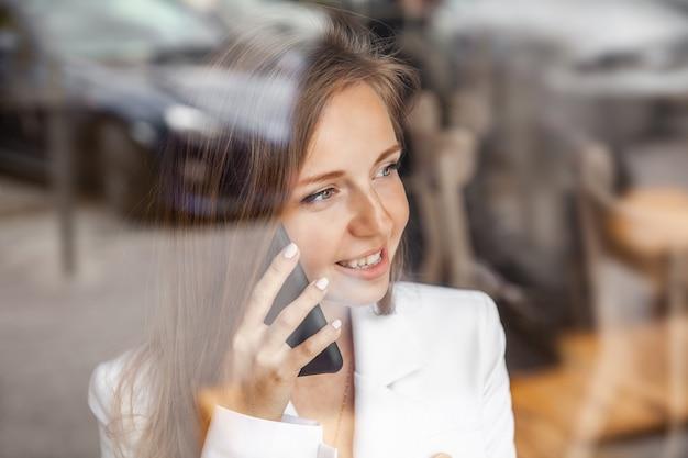 Close-up van gelukkige glimlachende vrouw die op mobiele telefoon spreekt die door venster kijkt