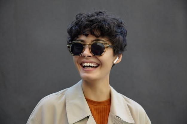 Close-up van gelukkige jonge brunette krullende vrouw met casual kapsel trendy zonnebril en casual kleding dragen, opzij kijken met charmante glimlach tijdens het lopen op straat