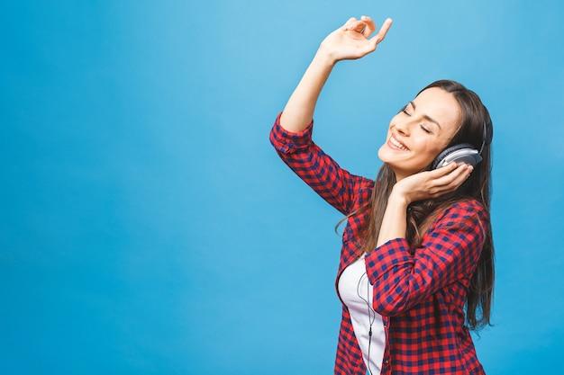 Close up van gelukkige jonge dame permanent met behulp van telefoon luisteren muziek in hoofdtelefoons
