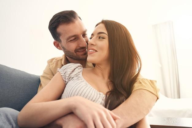 Close up van gelukkige jonge man en vrouw omarmen op een zachte bank in de woonkamer