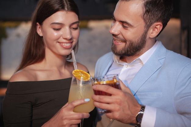 Close up van gelukkige jonge paar rammelende cocktailglazen, genieten van drankjes aan de bar