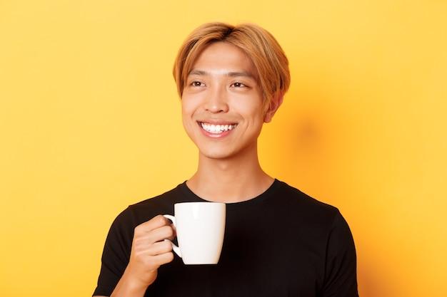 Close-up van gelukkige knappe jonge aziatische kerel met blond haar, dromerig en glimlachend terwijl het drinken van koffie of thee, die zich over gele muur bevindt.