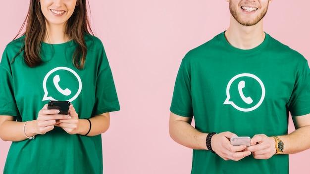 Close-up van gelukkige man en vrouw die mobiele telefoon houden