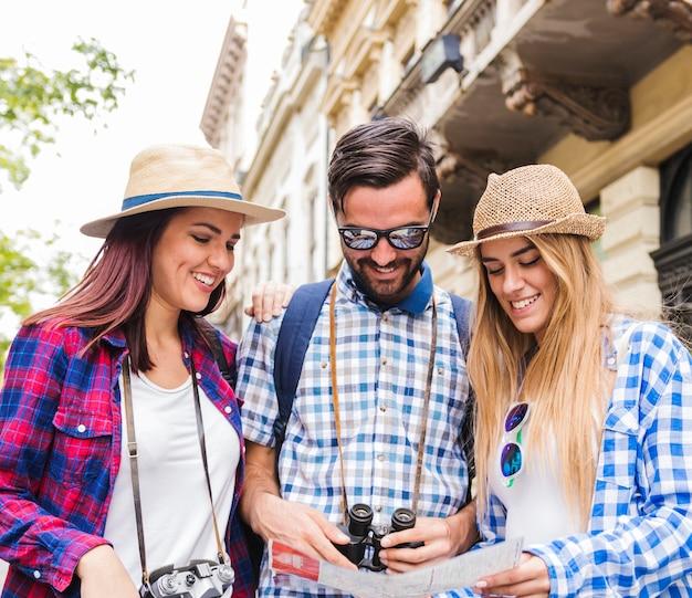 Close-up van gelukkige mannelijke en vrouwelijke wandelaars die kaart bekijken