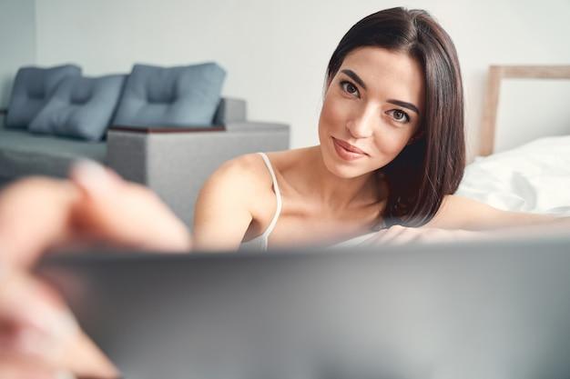Close up van gelukkige mooie vrouw met donker haar met behulp van gadget in de slaapkamer van haar appartement