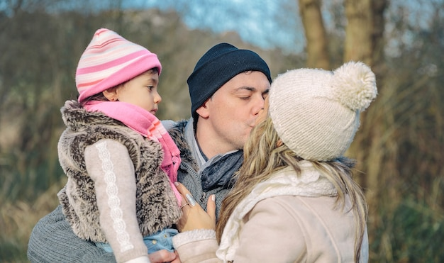 Close-up van gelukkige paar met haar dochtertje zoenen over een bos achtergrond. familie liefde concept.