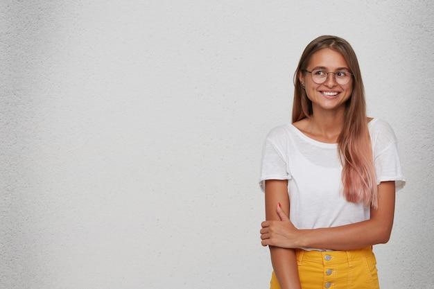 Close-up van gelukkige schattige jonge vrouw draagt t-shirt, gele rok en bril bijt op haar lip en kijkt naar de kant geïsoleerd over witte muur