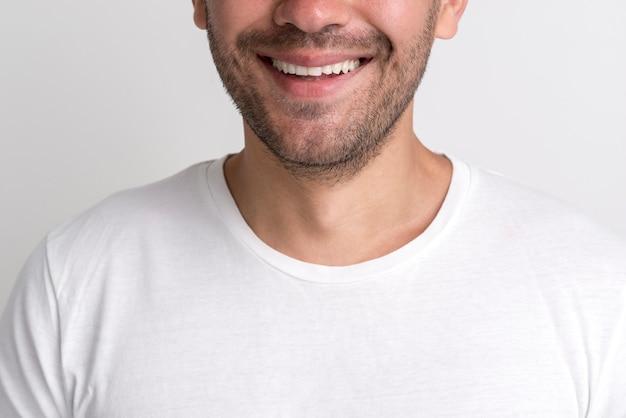 Close-up van gelukkige stoppels jonge man tegen witte achtergrond