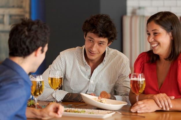 Close-up van gelukkige vrienden die aan tafel zitten