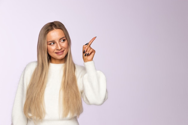 Close-up van gelukkige vrouw die en naar boven wijzende vinger richt, lege exemplaarruimte met haar vinger, zachte violette muur toont.