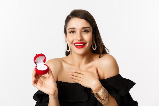 Close-up van gelukkige vrouw die haar verlovingsring toont, huwelijksaanzoek ontvangt, ja zegt, staande op witte achtergrond.