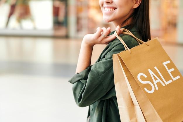 Close-up van gelukkige vrouw in groen shirt met papieren zak met verkoop inscriptie in winkelcentrum