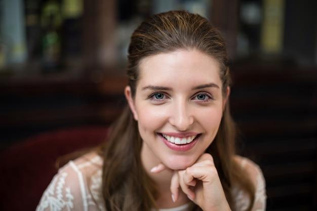 Close-up van gelukkige vrouw met handen op kin