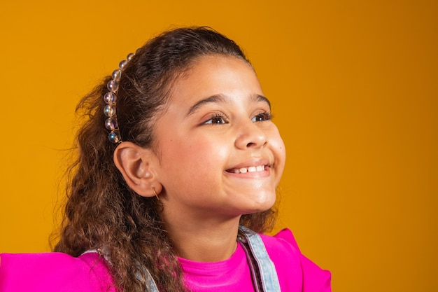 Close-up van gemengd meisje dat op gele achtergrond glimlacht. gemengd rasmeisje met gelukkig golvend haar. kinderdag