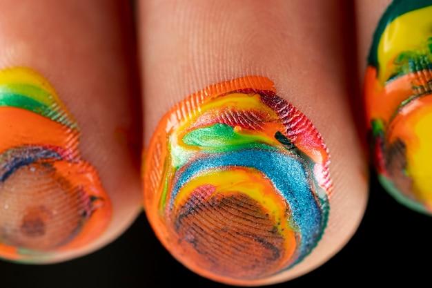 Close-up van gemengde verf op vingers