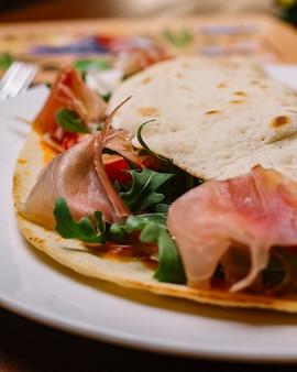 Close up van genezen vlees wrap met raket cherry tomaat en tomatensaus