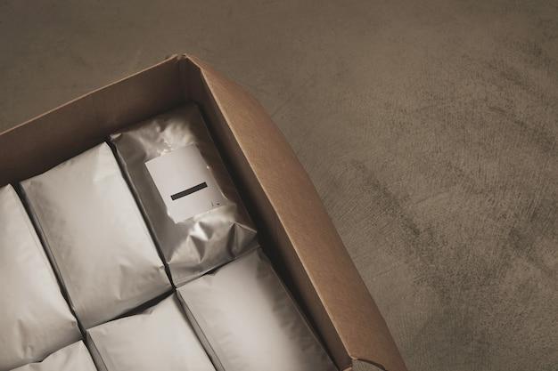 Close-up van geopende grote kartonnen doos vol met witte pakketten