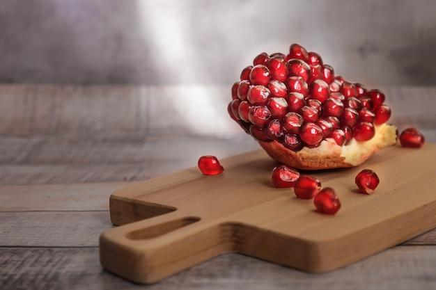 Close-up van gepelde granaatappelpartjes en granaatappelzaden op een houten bord in zonlicht.