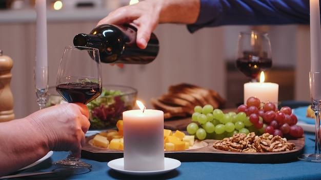 Close up van gepensioneerde senior man gieten van rode wijn in vrouw glas. romantisch gepensioneerd oud echtpaar vierend bij kaarslicht, liefde en jubileum
