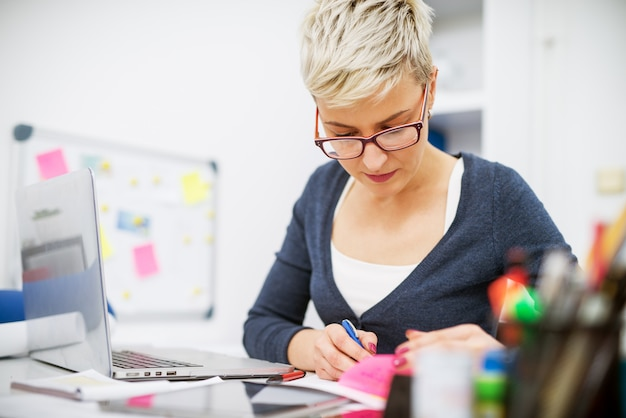 Close up van gerichte mooie middelbare leeftijd zakenvrouw werken aan het bureau in het kantoor met papieren en een laptop.