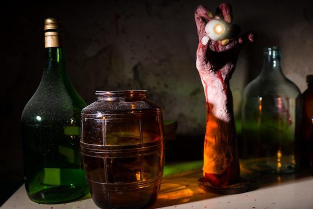 Close up van gerimpelde hand met oogbol tussen glazen potten met bloed bespatte muur in een halloween horror concept