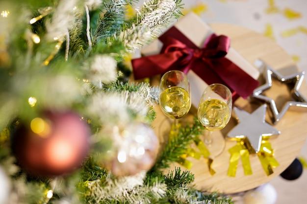 Close up van geschenkdoos, champagne en sterren in de buurt van versierde kerstboom