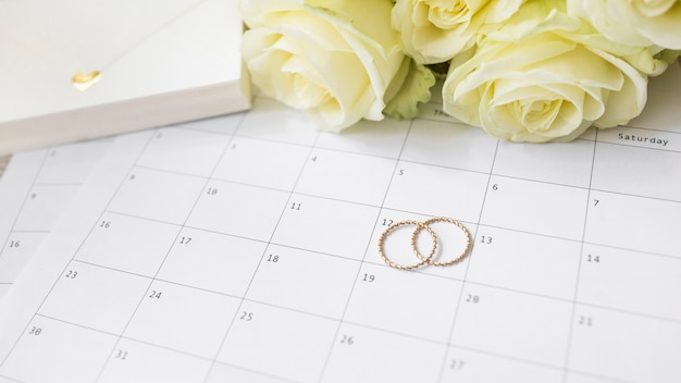 Close-up van geschenkdoos; rozen en trouwringen op kalender