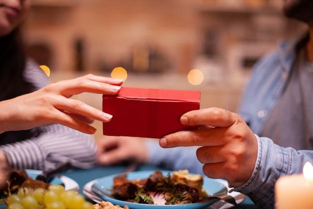 Close up van geschenkdoos vastgehouden door man en vrouw tijdens een romantisch diner
