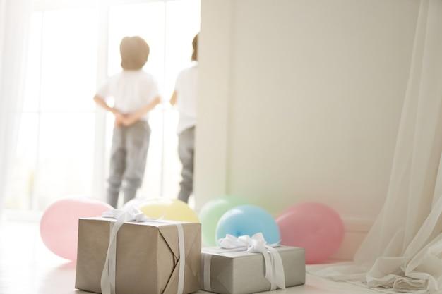 Close-up van geschenkdozen en kleurrijke ballonnen voorbereid voor het vieren van vakantie met twee nieuwsgierige latijns-tweelingjongens, kinderen die op de achtergrond staan. vakantie, cadeautjes, kinderconcept