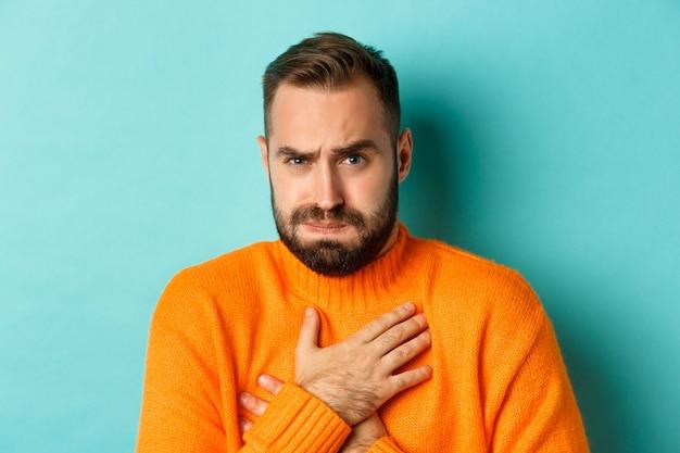 Close-up van geschokt en geschrokken man die chesk aanraakt, ontevreden en bezorgd kijkt, staande tegen een lichtblauwe achtergrond.
