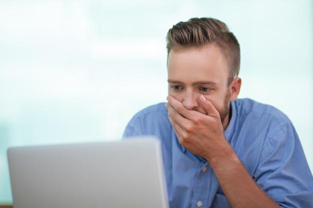 Close-up van geschokt jonge man die op laptop