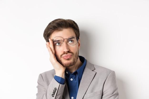 Close-up van geschokt vermoeide kantoormedewerker opstijgt bril en staren rechtsboven met droevig gezicht, witte achtergrond.