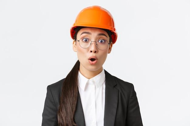 Close-up van geschokte en bezorgde aziatische vrouwelijke ingenieur hoort slecht nieuws, verontrustende aankondiging, staande in veiligheidsmasker, bril en pak en hijgend geschrokken, witte achtergrond