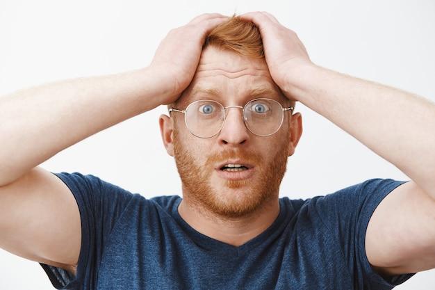 Close-up van geschokte gealarmeerde roodharige man die op zijn hoofd sloeg en in paniek raakte, iets vergeten