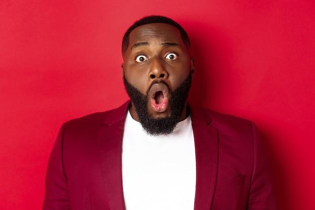 Close-up van geschokte zwarte man hijgend en laten vallende kaak onder de indruk, starend naar de camera, staande over rode achtergrond.