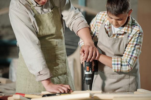Close-up van geschoolde timmerman in schort handen van zoon duwen terwijl hij hem helpt om houten oppervlak in werkplaats te boren